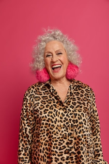 グラマー大喜びの年配の女性は、誰かに楽しまれ、特別な日のためにファッションの服を着て、ピンクの背景で隔離されて、楽しく笑います。スタイリッシュなヒョウの衣装で成熟した女性