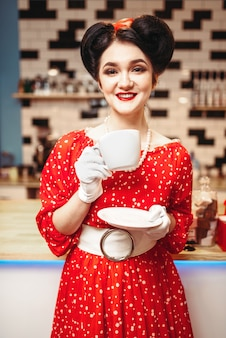 グラマーピンナップガールはレトロなカフェでコーヒーを飲む