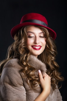 Glamour portrait of beautiful woman model with red lips and long brunette hair in luxury fur coat and hat color marsala