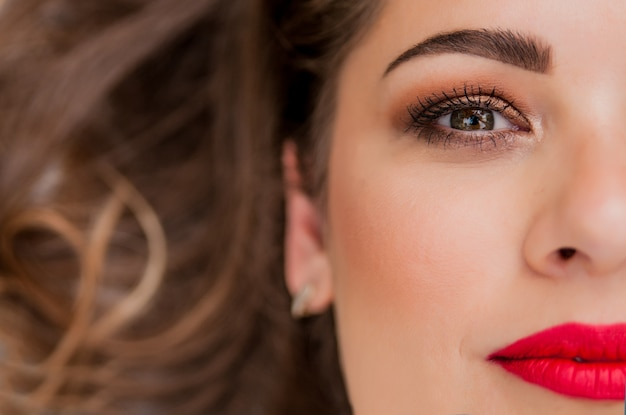 新鮮な毎日の化粧とロマンチックな波状の髪型を持つ美しい女性モデルの魅力的な肖像画。ファッション光沢のある蛍光灯、肌にセクシーな光沢のある唇のメイクとダークな眉毛
