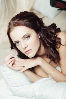 グラマーの肖像画-ベッドでランジェリーのセクシーな美しい女性