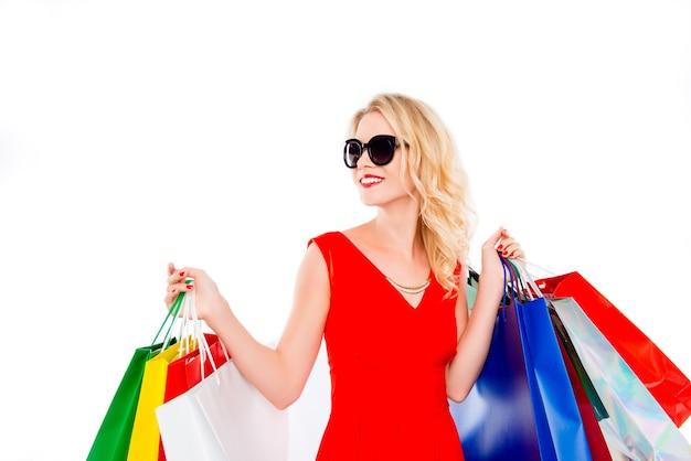 ショッピングをしているパケットとメガネの魅力的なきれいな女性