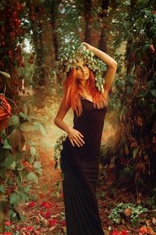屋外の魔法の森でホップの花輪を持つ魅力的な赤毛の女性