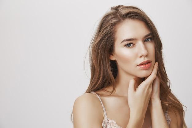 美しいきれいな肌に触れるグラマー官能的な女性
