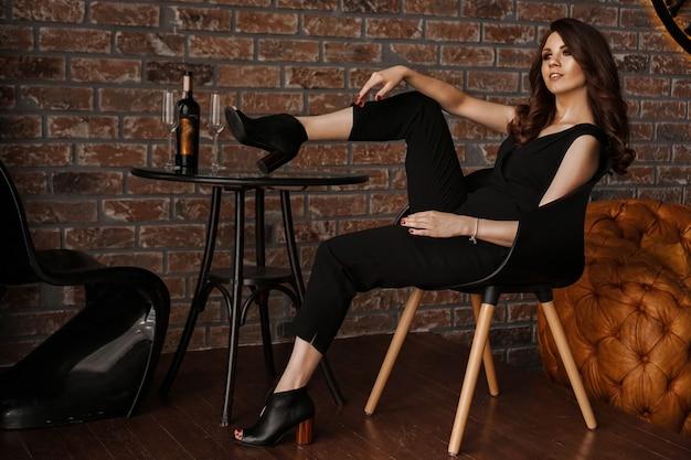 テーブルの上に足でロフトレストランに座っている長い髪の魅力的なセクシーな若い自信のある女性