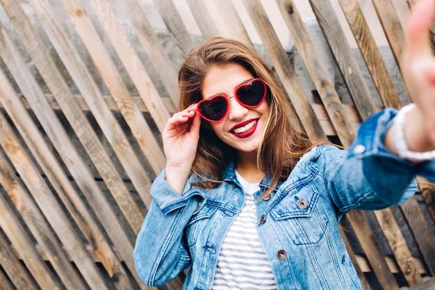 Glamour ragazza sorridente indossando occhiali cuore tenendo il telaio. close-up ritratto di affascinante giovane donna graziosa toccando la fotocamera.
