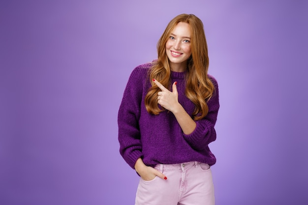 Glamour ed elegante donna femminile con lunghi capelli rossi naturali in maglione viola che tiene la mano in tasca mentre indica l'angolo in alto a sinistra che mostra il posto in cui fa l'acconciatura o il trucco sul muro viola.
