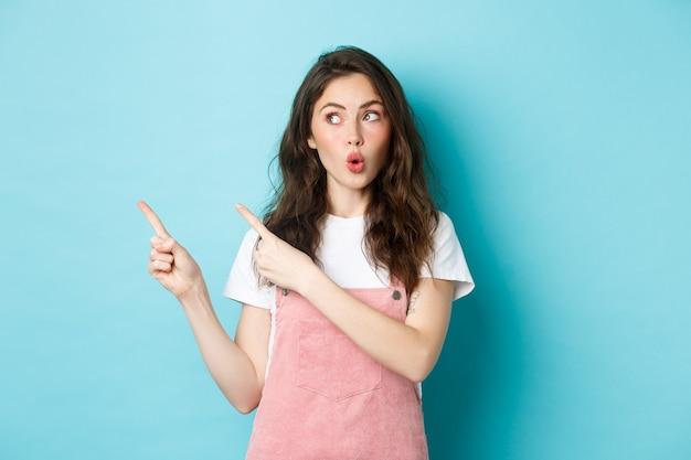 グラマー夏の女の子は唇をパッカーし、すごい、面白いプロモーション取引を指差して左を見て、広告を表示し、青い背景に立って言う