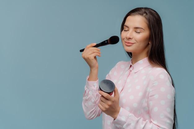 グラマー女性は化粧ブラシで赤面を適用します