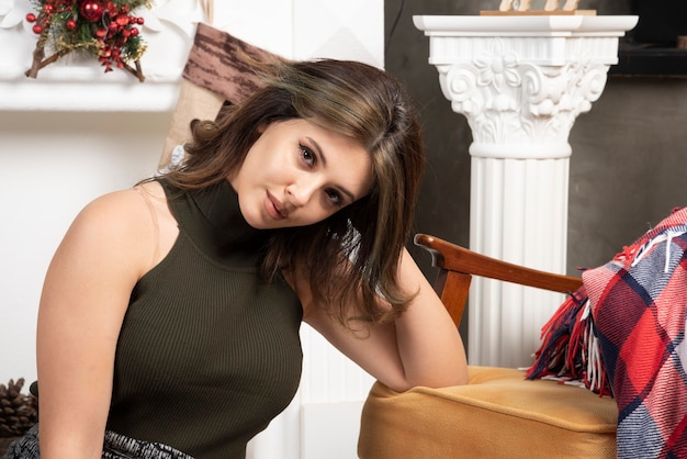 Donna glamour in top nero seduto su un tappeto bianco vicino al caminetto
