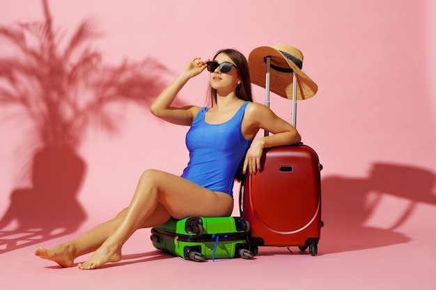 Гламурная женщина в купальнике сидит на разноцветных чемоданах