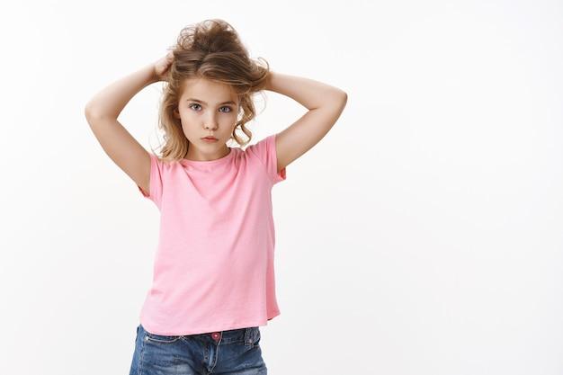 ピンクのtシャツで青い目をしたグラマーな若いかわいい金髪の小さな女の子の子供は、髪を上げ、髪のお団子を作り、柔らかく見え、ファッション凝視カメラ、真剣な決意の表現、白い壁に立つ