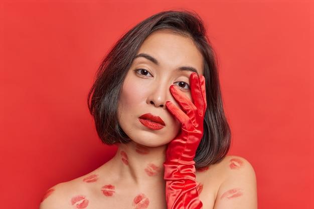 매력적인 젊은 여성 모델은 카메라를 직접 쳐다보고 얼굴에 손을 대고 선명한 붉은 벽에 셔츠를 입지 않은 채 실내에서 머리를 기울인 자연스러운 아름다움을 가지고 있습니다.