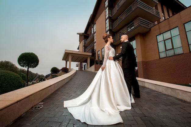 Glamour young just married couple in wedding suits outdoors