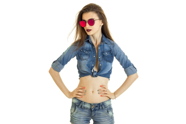 Glamour young lady in denim clothes and sunglasses without bra isolated on white