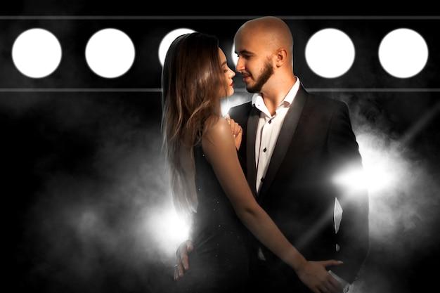 ライトが付いている黒い煙の壁のスタジオでポーズをとる黒いスーツとドレスの魅力的な若いセクシーなカップル