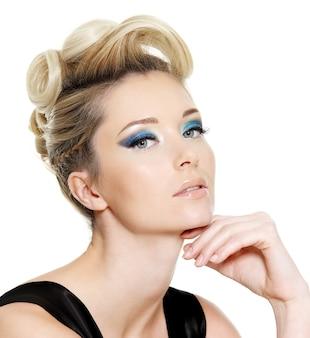 파란 눈 화장과 흰색 공간에 곱슬 헤어 스타일을 가진 매력적인 젊은 여자