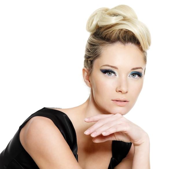 Giovane donna glamour con trucco degli occhi azzurri e acconciatura riccia su sfondo bianco
