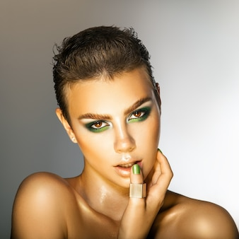 スタジオの灰色の背景でカメラを見て緑の色の化粧の魅力的な若い女性