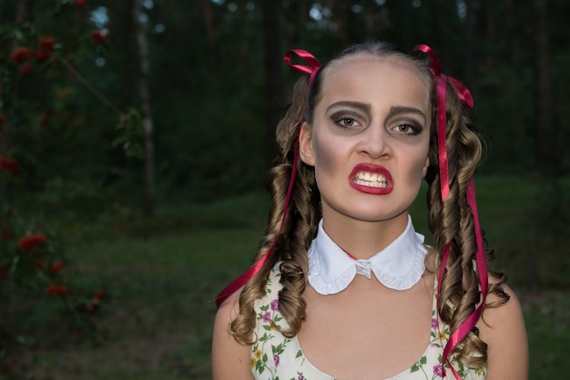 Glamour zombie girl with ringlets as at a doll  . halloween concept. forest background. halloween make up.