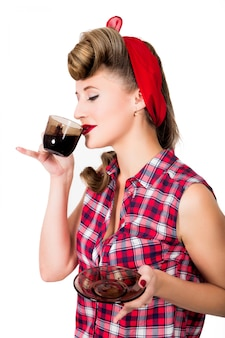 Glamourous pinup girl holding a cup of hot coffee or tea
