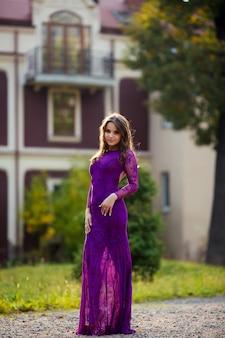 Glamourous woman with long dark hair in elegant purple dress posing outdoors