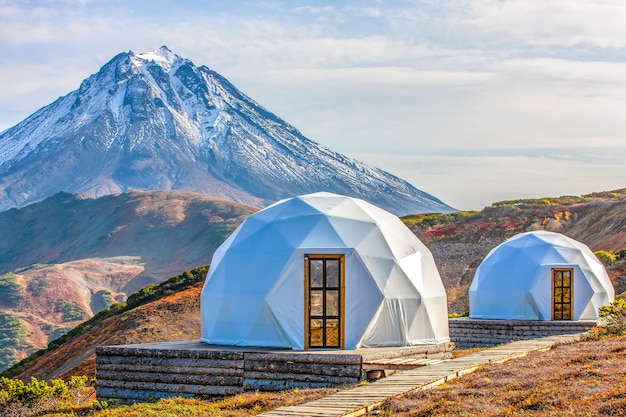 Glamping house and volcano rural landscape tent houses in kamchatka peninsula selective focus