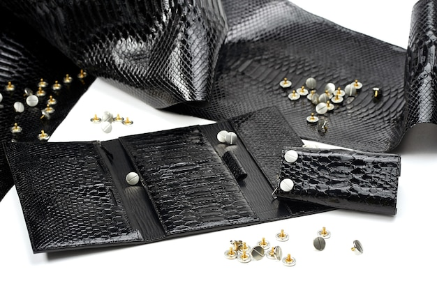 Glancy black leather pieces lay near woman s wallet with many sectors. they include snake s skin immitation. the material lays on the white background. also there are metallic studs near it.