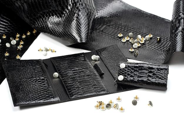 Рядом с женским кошельком с множеством секторов лежали блестящие черные кожаные изделия. они включают имитацию змеиной кожи. материал ложится на белый фон. также рядом есть металлические шпильки.