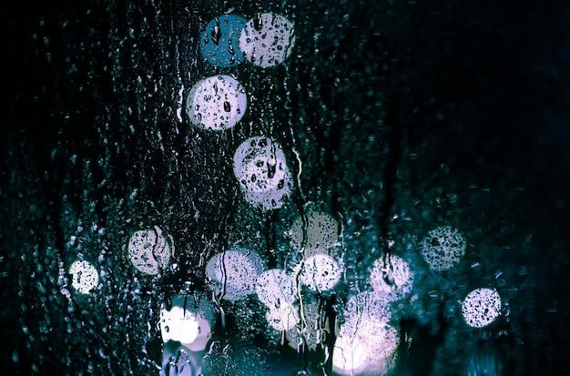 Ослепление ночного города через окно в каплях дождя