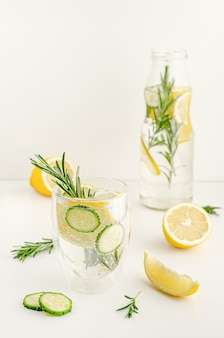 A glas of refreshing summer lemonade or detox water with lemon and rosemary on white table. healthcare concept. copy space