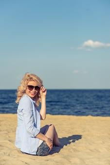 Молодая женщина на пляже в glasess.