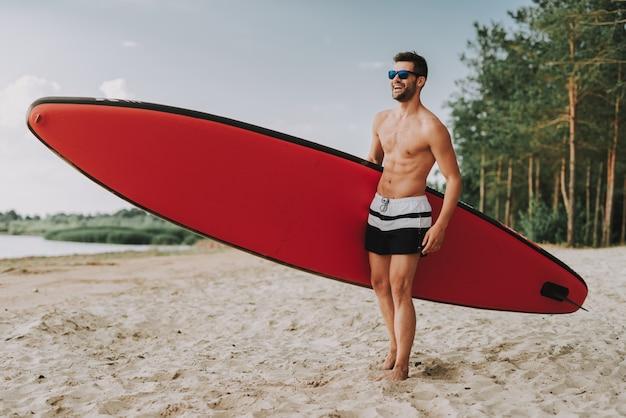 Glasessのビーチの上に立ってサーフィンを持つ運動男