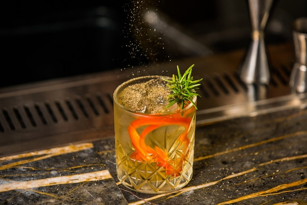 A glass of alcohol cocktail with rosemary leaves, ice cubes and orange spaghetti skin