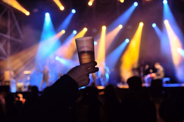 A glass of alcohol at a concert of live music