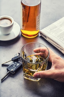 Glass of alcohol hand man the keys to the car and irresponsible driver.