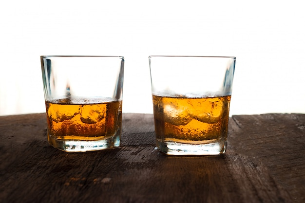 Glass of alcohol scotch whiskey with ice on wooden table