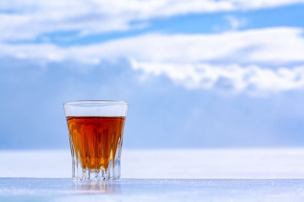 Glass of alcohol stands on ice plate against the sky with clouds with copy space