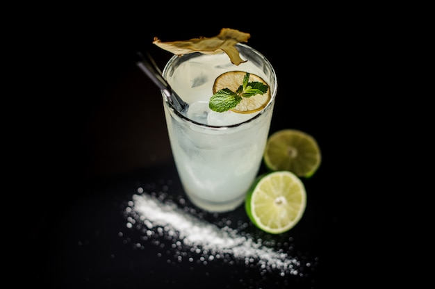 Glass of alcoholic cocktail with a straw decorated with a slice of lime