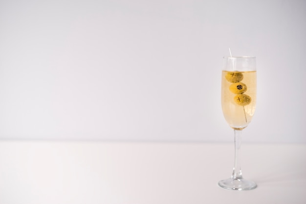 Glass of alcoholic drink with olives on white background