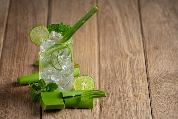 Bicchiere di succo di aloe vera messo sul pavimento di legno