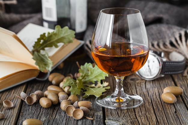 Glass of amber color whisky in glass on oak table