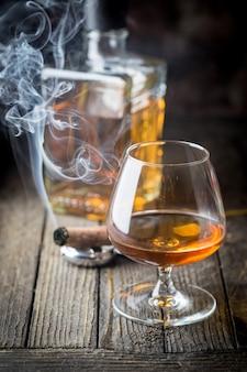 ガラスとブランデーまたはコニャックのボトルと木製のテーブルの上に喫煙葉巻。