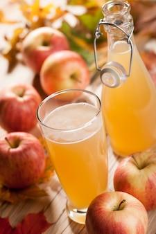ガラスとリンゴジュースのボトル、リンゴ、木製のテーブルに落ち葉
