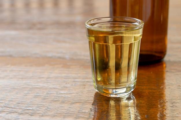 Стакан и бутылка кашасы, типичного бразильского напитка.