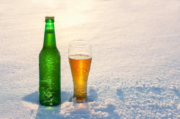 해질녘 눈 속에서 시원한 맥주 한 병 아름다운 겨울 배경 야외 레크리에이션 알코올 음료 광고 술과 휴일