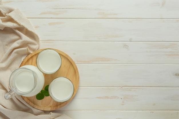 白い木の表面にガラスとミルクのボトル