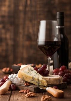 ボード上のさまざまなチーズと木製のテーブルの背景にブドウの選択と赤ワインのガラスとボトル。ブルースティルトン、レッドレスター、ブリーチーズとナイフ。