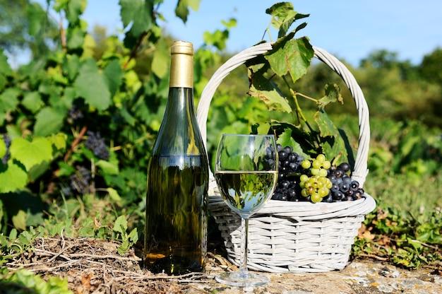 ガラスとワインのボトルとバスケットのブドウ