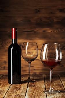 유리와 테이블에 맛있는 레드 와인 병
